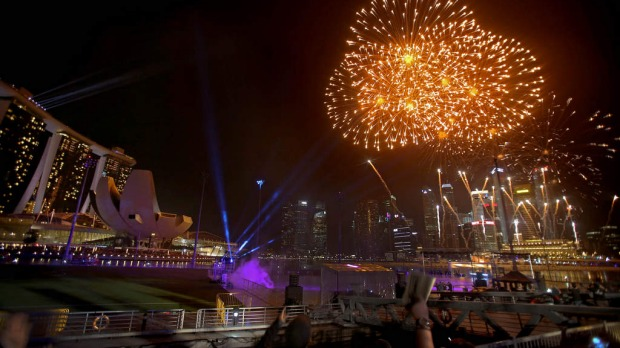 Fireworks explode over the Singapore financial district to mark the start of the new year .