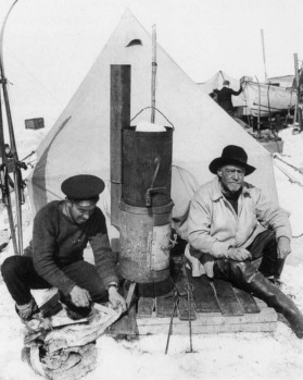 Photographer Frank Hurley & Sir Ernest Shackleton sit before the entrance to their tent.  Hurley (left) is skinning a ...