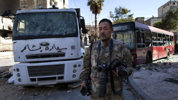 Japanese trucker Toshifumi Fujimoto holds his cameras in front of damaged buses in Aleppo's old city in Syria.