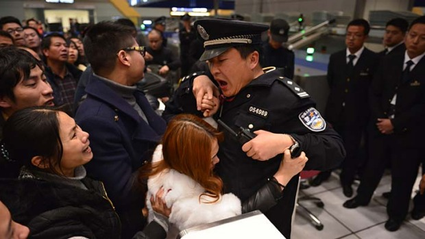 Stranded travellers argue with police and airport officials at Changshui International Airport.