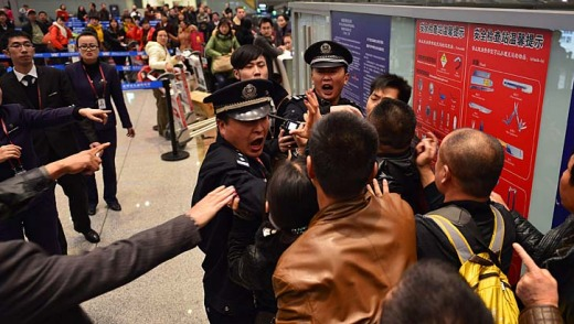 Stranded travellers argue with police and airline personnel at Changshui International Airport.