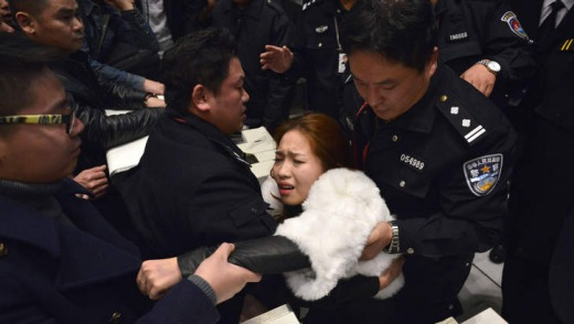 A woman is helped by police and airline personnel after being pushed by the crowd of stranded travellers.