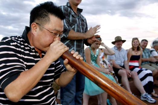 World Heritage listed Uluru in Australia's Northern Territory. Tourist playing a didgeridoo at the Sounds of Silence.