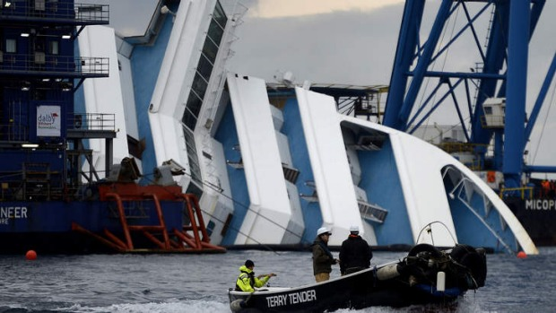 Workers pass on a small boat near the Costa Concordia cruise ship during salvage operations.