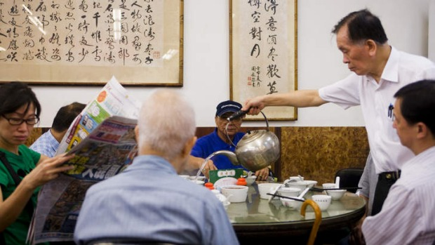 Atmospheric ... a waiter pouring tea for yum cha diners at Lin Heung Tea House in Hong Kong.