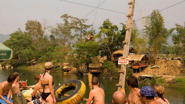 Tourists enjoy one of Vang Vieng's riverside bars. In the wake of several high-profile deaths, a crackdown by ...
