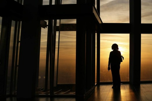 An employee poses during sunrise as she looks out the window from The View gallery at the Shard, western Europe's ...