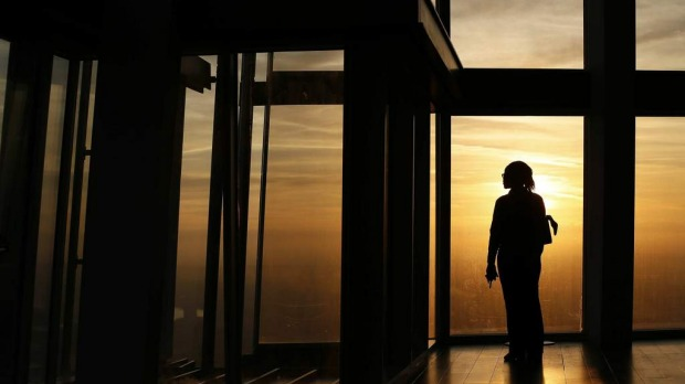 An employee poses during sunrise as she looks out the window from The View gallery at the Shard, western Europe's tallest building.