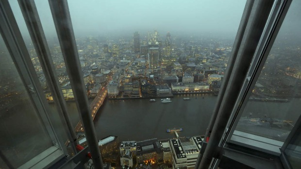 Commercial real estate and office buildings are seen illuminated in the early morning and viewed from 'The View From The Shard', a series of viewing galleries near the top of the Shard tower in London, U.K.