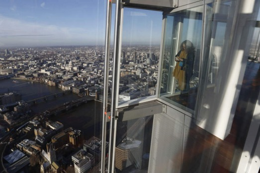 "A woman taking pictures of the view of London from the 68th floor of ""The Shard"" in central London, Europe's tallest ..."