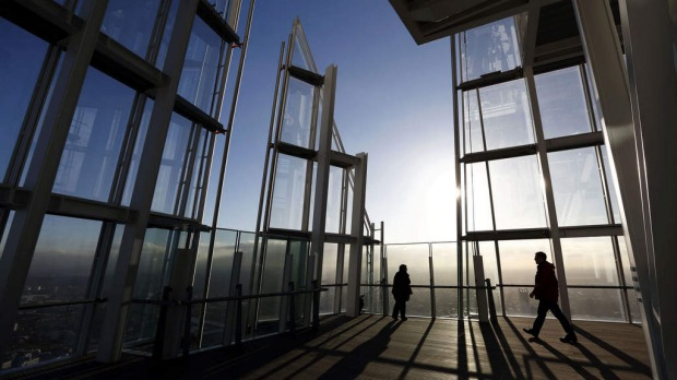 "People admiring the view of London from the 68th floor of ""The Shard"" in central London. The 310-metre Shard has been described as too high, too audacious and too likely to cast its shadow over the historic monuments nearby - and too costly at a time of austerity."