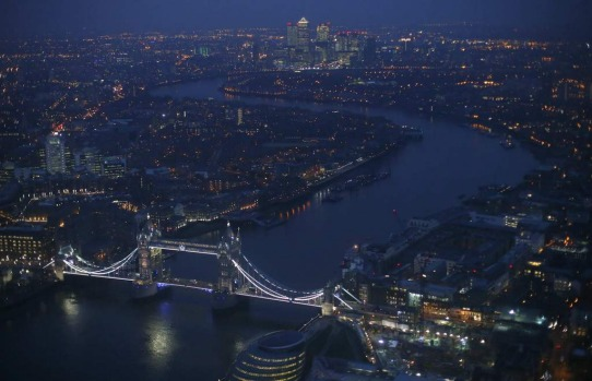Tower Bridge and the Canary Wharf financial district (at rear) are seen at dusk in an aerial photograph from The View ...