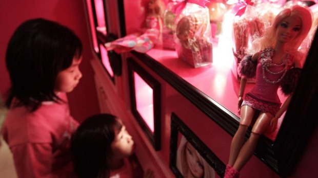 Girls look at Barbie dolls on display during the media preview of the Barbie-themed cafe in Taipei.