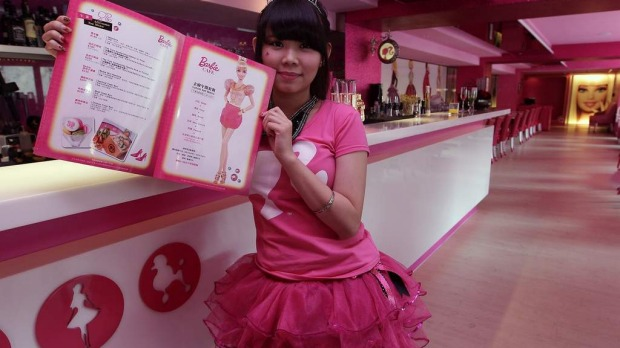 A waitress poses with a menu during the media preview of the Barbie-themed cafe in Taipei.