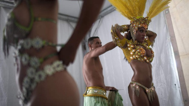 Samba dancer Diana Prado, right, is with her costume as she prepares for a carnival parade at central station in Rio de Janeiro, Brazil.