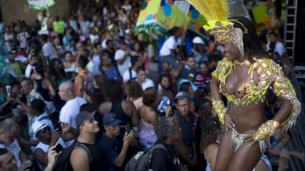 "Samba dancer Diana Prado performs during a carnival parade at central station in Rio de Janeiro, Brazil. Prado spends her daylight hours working as a supervisor at a call center. At night, she is a samba dancer, or ""passista,"" as they're known in Portuguese."