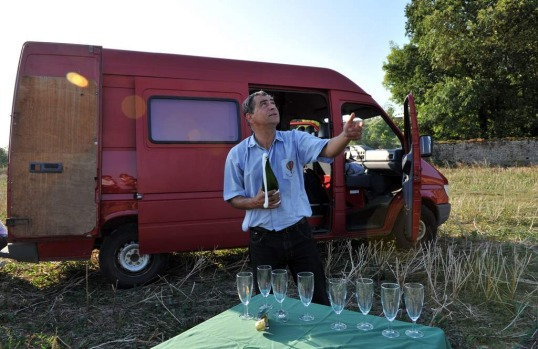Vincent Dupuis, champion hot air balloon pilot, opens a bottle of champagne for guests and crew in a farm paddock in ...