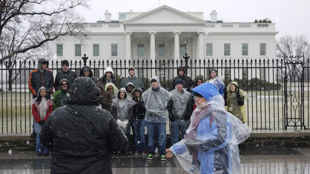 A tour group poses for a photo in front of the White House. The US government has cancelled its visitor tours of the ...