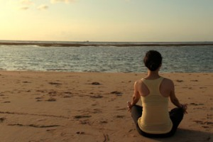 Young fit woman doing yoga by the beach.