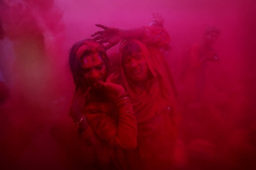 People dance as coloured powder is thrown in Barsana, India.