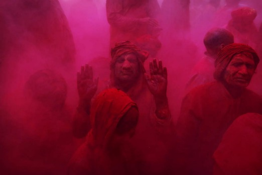 Hindu men and a boy from the village of Nangaon are covered in colored powder.