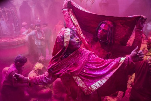 Hindu devotees dance as others play with colour in the village of Barsana, India.