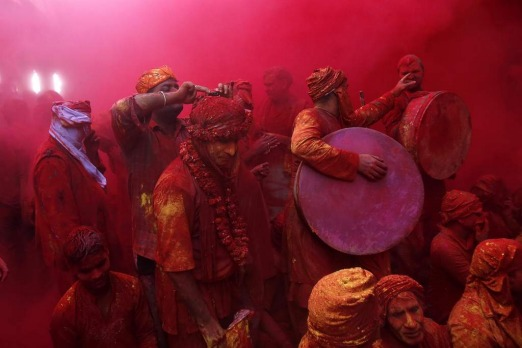 Members of a band stand in a cloud of coloured powder inside a temple at the village of Barsana, India.