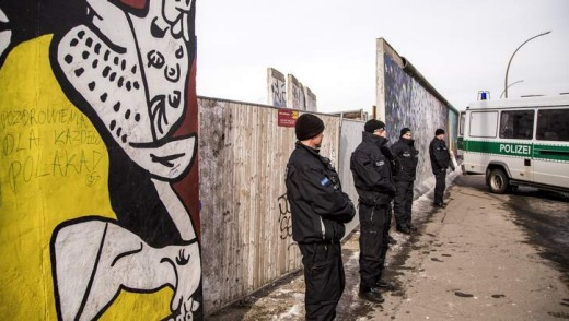 Policemen stand guard next to a section of the Berlin Wall which has been removed to make way for a luxury apartments ...