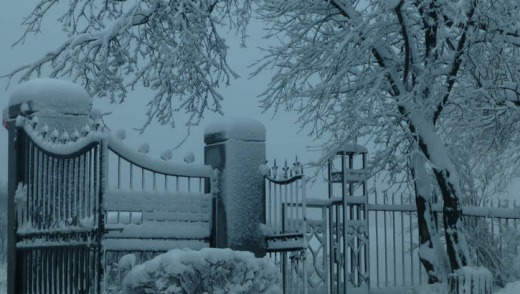Snow-covered cemetery gates.