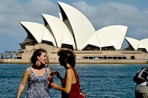 Tourists pose for photographs before the Sydney Opera House
