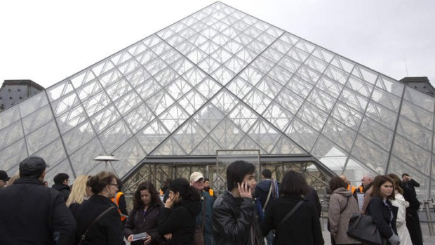 Visitors stand in front of the entrance to the closed Louvre museum.