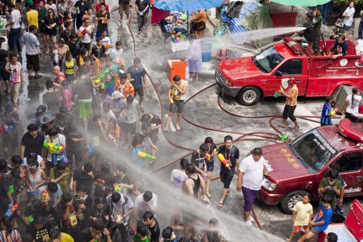 Thai fire fighters soak the crowd with their fire hoses during a community water fight on Silom Road.