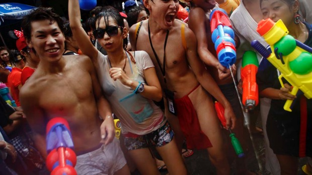 Revellers use water guns as they participate in a water fight during Songkran Festival celebrations at Khaosan road in Bangkok.