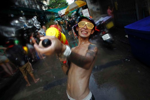 A reveller uses a water gun as he participates in a water fight during the Songkran Festival celebrations at Khaosan ...