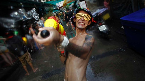 A reveller uses a water gun as he participates in a water fight during the Songkran Festival celebrations at Khaosan road in Bangkok.