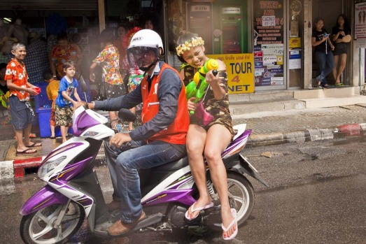A Thai woman on a motorcycle taxi participates in a waterfight during the Songkran water festival.