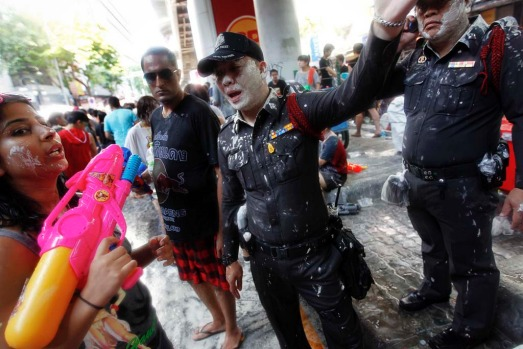 Policemen talk to revellers participating in a water fight during Songkran Festival celebrations.