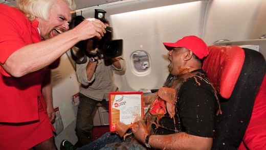 Richard Branson 'accidentally' spills a tray of drinks on AirAsia chief Tony Fernandes.