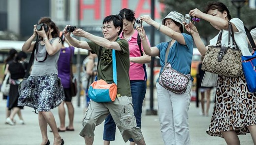 Mainland Chinese tourists take pictures during a visit to Hong Kong.