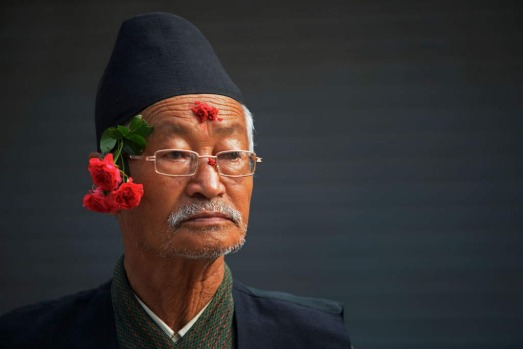 A Nepalese bystander, seen with roses in his traditional headgear, looks on during a procession for Everest summitteers ...