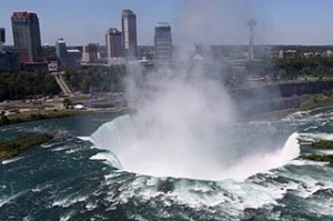 The town of Niagara Falls, Canada is seen past a cloud of mist rising over Horseshoe Falls, the largest of the Niagara Falls
