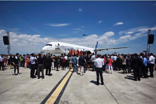 A crowd watches as the crew emerge from an Airbus A350 following its first flight.