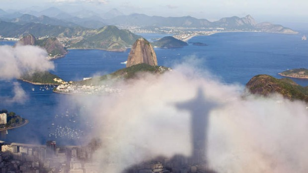 The shadow of the Christ the Redeemer statue floats over Rio de Janeiro and Sugar Loaf.
