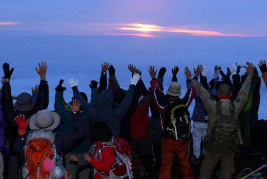 Climbers raise their hands to celebrate the sunrise on the summit.
