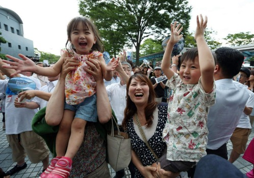 Local residents raise their hands to celebrate as UNESCO granted World Heritage status to Japan's Mount Fuj.