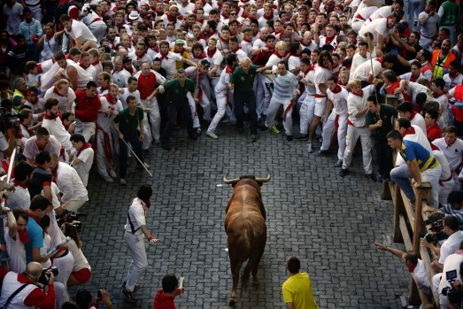 An Alcurrucen's ranch fighting bull runs towards revelers during the running of the bulls of the San Fermin festival, in ...
