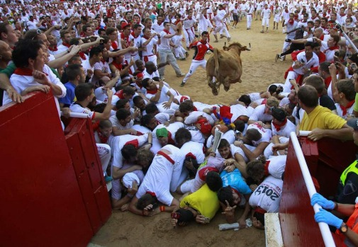 A fighting cow leaps over revellers upon entering the bullring following the first running of the bulls of the San ...