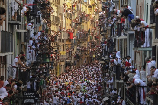 People standing on balconies look at participants as they run in front of Alcurrucen's bulls during the first bull run ...