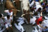 Runners fall in the path of an Alcurrucen fighting bull (L) and steers at the entrance to the bull ring during the first ...