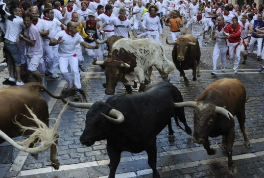 Runners sprint alongside Alcurrucen fighting bulls at the Estafeta corner during the first running of the bulls of the ...